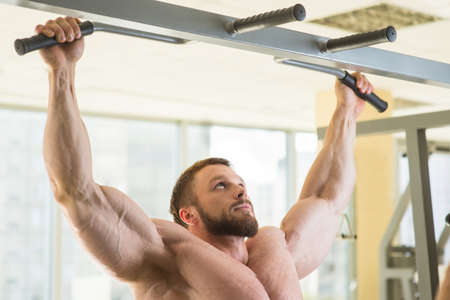 pullups: Bodybuilder doing pull-ups. Muscular man in gym. Strong man preparing for competitions in gym. Sportsman gaining his point.