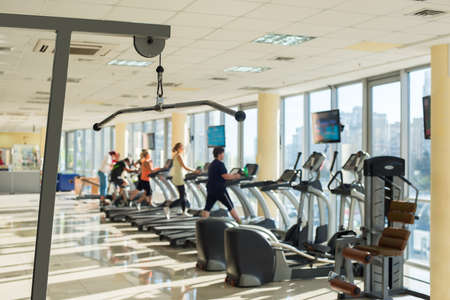 apparatus: Training apparatus in gym. Picture of gym hall with training apparatus. People exercising in gym on background. Stock Photo