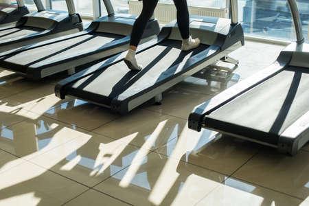 Treadmills in gym hall. Womans muscular legs on treadmill.