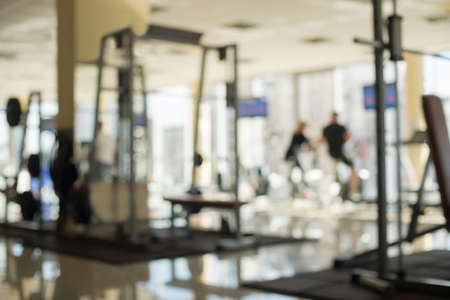 phon: Picture of a gym hall. Blurred picture of gym. Woman and man are working out in gym. Woman and man burn calories on the exersice bikes.