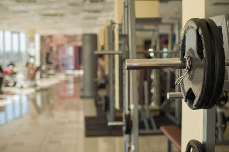 lifestile: Training apparatus in gym. Barbells hanging on metal rack in gym hall. Different apparatus on the background.