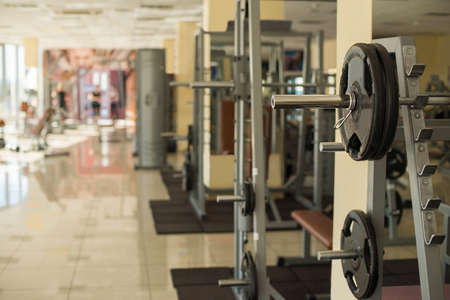 gripping bars: Trainers in gym hall. Barbells hanging on metal rack in gym hall. Different apparatus on the background.