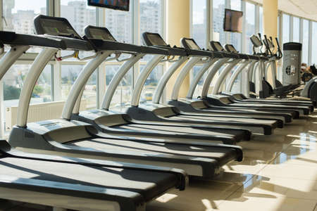 exercices: Treadmills in gym. A few treadmills at the window in gym. Training apparatus in gym hall. View from the window. Stock Photo