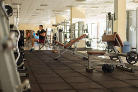 upper floor: Trainers in gym. Training apparatus in gym. Sportsman is working out in gym. Strong man doing exersices in gym.