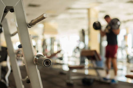 achiever: Sportsman with barbell. Blurred picture of a man on the background. Strong man standing in gym. Stock Photo