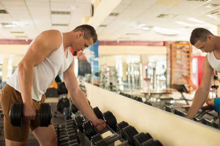 sportsmen: Young guy in gym. Sportsmen standing at the mirror in gym. Guy taking dumbbells. Stock Photo