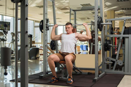 brawny: Strong guy with barbell. Sportsman concentrated on the sport. Young man is pushing barbell.