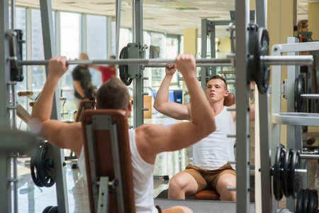 lusty: Young bodybuilder lifts weights. Athlete working out in gym. Men training on the background near the window in gym. Stock Photo