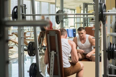 lusty: Young bodybuilder in gym. Athlete working out in gym. Sportsmen looking at the mirror in gym. Stock Photo