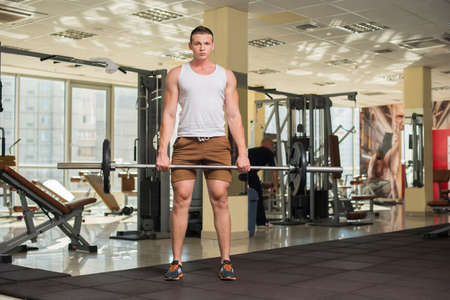 lusty: Young sportsman in gym. Strong guy standing with barbell in gym. Man working out in gym on the background.