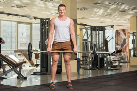 lusty: Young sportsman in gym. Strong guy standing with barbell in gym. Fitness stations on the background.