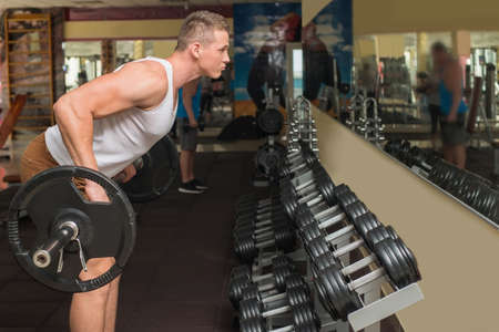sportsmen: Young guy in gym. Sportsmen standing at the mirror in gym. Guy taking barbell and looking at the mirror in gym. Stock Photo