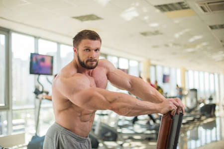 lusty: Muscular man. Strong muscular man looking straight at the camera. Bodybuilder with huge muscles in gym. Stock Photo