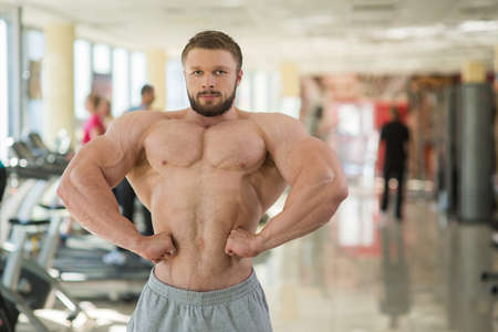 lusty: Muscular man in gym. Strong muscular man looking straight at the camera. Bodybuilder showing his huge muscles. Stock Photo