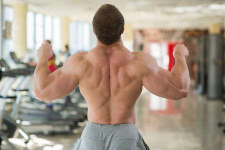 Muscular mans back. Bodybuilder showing his strong back and arms.