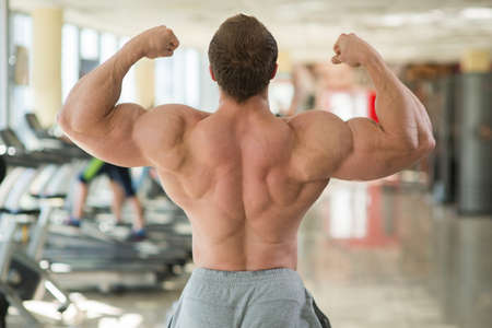 achiever: Muscular mans back. Muscular man's back. Bodybuilder showing his strong back and arms. Stock Photo