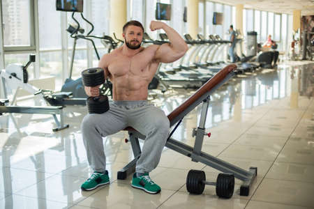 brawny: Muscular man in gym. Bodybuilder showing his strong muscular arm. Sportsman keeping dumbbell in hand.