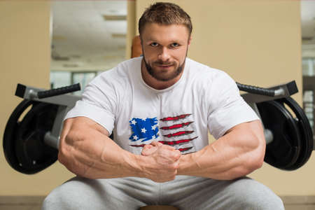 lusty: Bodybuilder in gym. Sportsman sitting at trainers. Mirror on the wall in gym. Stock Photo