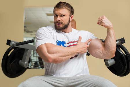 muscle: Hombre fuerte con enormes músculos. Deportista que muestra sus músculos. Foto de archivo