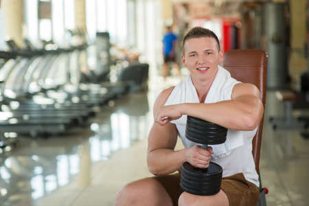 gym: Young sportsman in gym. Guy with towel on the neck in gym. Apparatus in gym on background. Stock Photo