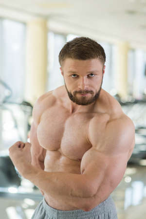 lusty: Muscular man. Strong muscular man looking straight at the camera. Bodybuilder with huge muscles.