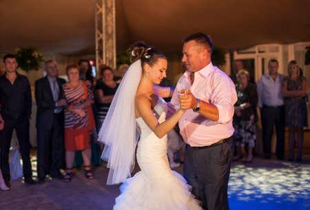 ウクライナ、オデッサ 07.09.2013。美しい花嫁は、ゲストのサークルで彼女の父親と一緒に踊っています。