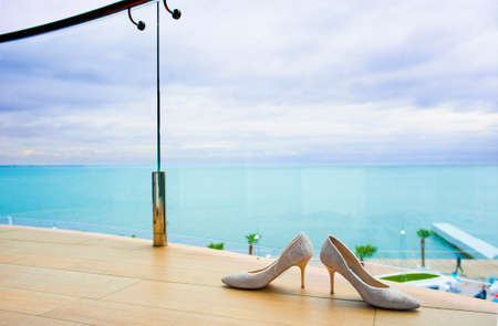 light hearted: Cute bridal shoes are standing near the balcony fencing. Stock Photo
