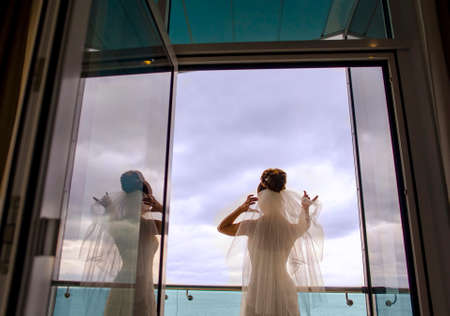 minx: The beautiful bride is standing on the balcony. The wind is blowing in her bridal veil. Stock Photo