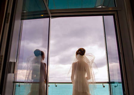 minx: Thel bride is standing on the balcony. The wind is blowing in her bridal veil.