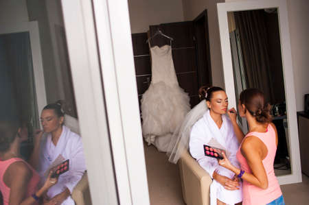 minx: The visagist is preparing the bride for the ceremony in hotel room.