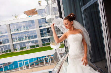 The coquette bride is touching her veil on the balcony.