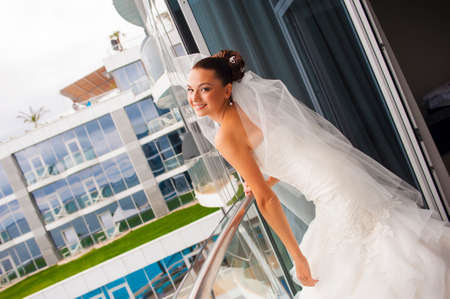 minx: Attractive bride is standing on the balcony, looking jilt and smile. Stock Photo