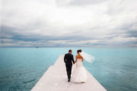 Newlyweds are walking on the sea berth.