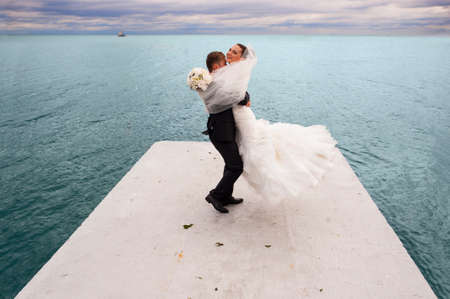 sea line: The groom is whirling his bride by the sea line and they are having fun.