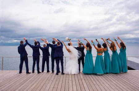 결혼식 축하 파티 참석자는 강 부두에 서서 손을 들고 게임을합니다. 스톡 콘텐츠