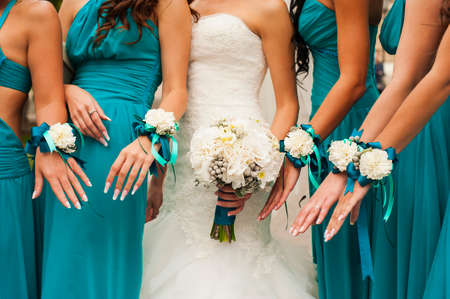 minx: The bride and bridesmaids are showing beautiful flowers on their hands. Stock Photo