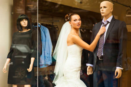 minx: The bride is touching the tie on mannequin in showcase.
