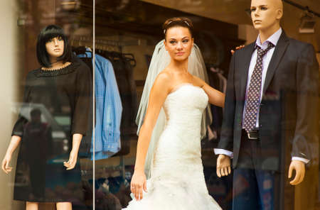minx: The pretty bride is standing in showcase between mannequins and smiling. Stock Photo
