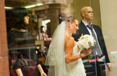 minx: The bride is standing in showcase between mannequins and smiling.