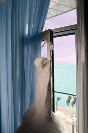 light hearted: The nice bridal dress is hanging on the window in the hotel room.