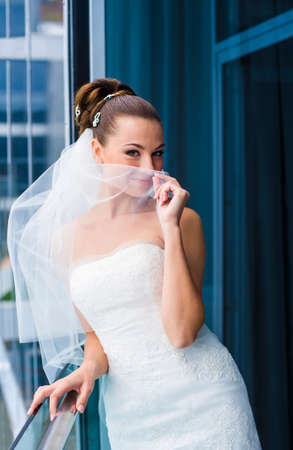 minx: Attractive bride is standing near the window, looking jilt and smile.