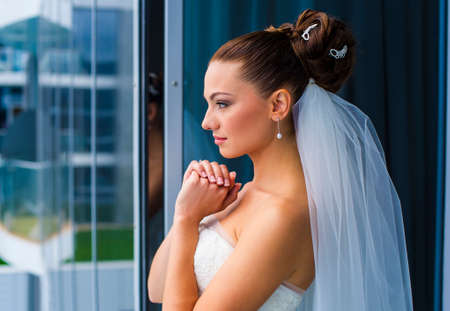 minx: Attractive bride is standing near the window and looking through.