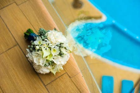 minx: Bride bouquet is lying near window opposite the swimming pool.