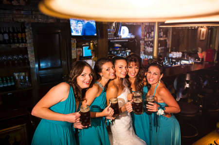 minx: Ukraine, Odessa 07.09.2013. The bride and bridesmaids are standing in the pub with beer and smiling. Editorial