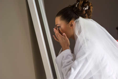 foretaste: The beautiful bride is correcting her makeup. She standing in front of the mirror.