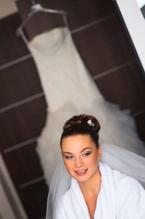 minx: The beautiful bride is speaking to the visagist during the preparation. Her wedding dress is hanging behind her. Stock Photo