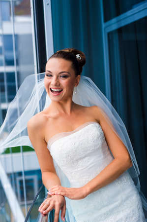 minx: Coquette bride is standing near the window. She is looking great and smiling. Stock Photo