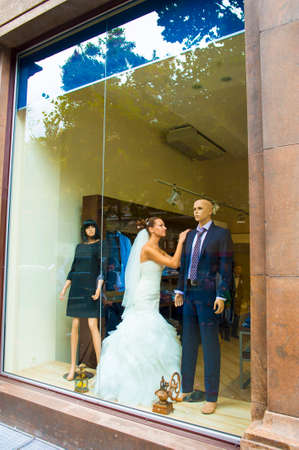 strictly: The bride is standing in showcase between mannequins. She is playing a role. Stock Photo