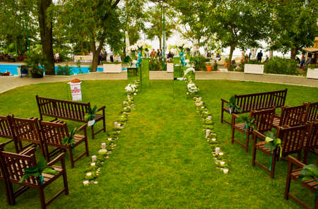 light hearted: Decoration glade in the park is ready for celebration. There are flowers and candles way on it. Stock Photo