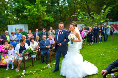 결혼식: 우크라이나 오데사 2013년 9월 7일. 아버지는 의식의 장소 신부를 선도하고 있습니다. 손님은 그들을보고있다. 에디토리얼